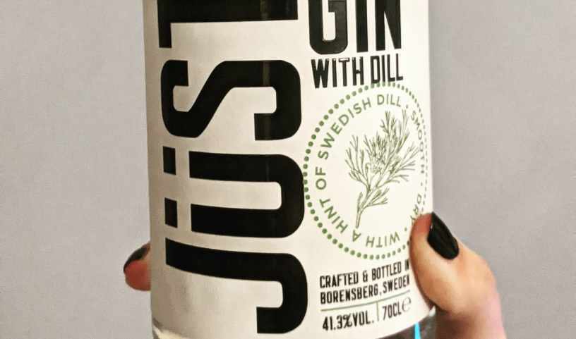 Close up of Jüst Gin bottle, held by a hand with black painted nails